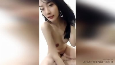 youthful asian dame with fake hooters is posing in the bed